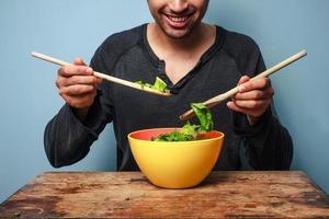 glücklicher Mann, der Salat mit Holzlöffeln mischt foto