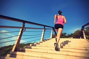 Sportfrau mit gesundem Lebensstil, die auf Steintreppen am Meer läuft foto