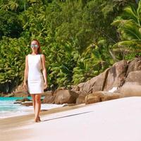 Frau, die Kleid am Strand auf den Seychellen trägt