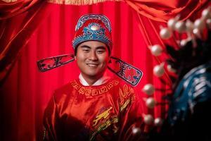 Porträt des schönen chinesischen Bräutigams, der sich in traditionelle Hochzeitskleider kleidet foto