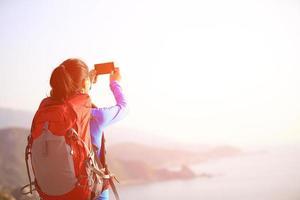 wandernde Frau benutzen Smartphone, das Foto macht
