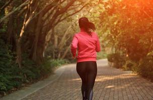Frau, die auf Bürgersteig im Waldweg joggt foto