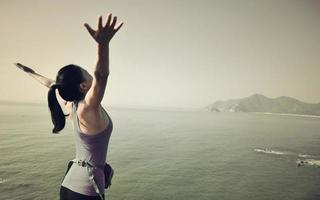 Wanderfrau hob die Arme zum blauen Meer foto