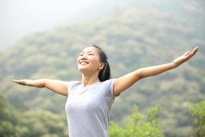 jubelnde Wanderfrau offene Arme am Berggipfel foto