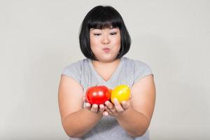 Porträt der schönen übergewichtigen asiatischen Frau, die Früchte hält foto