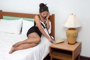 Frau, die vom Telefon auf dem Bett anruft foto