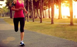asiatische Frau des gesunden Lebensstils, die am tropischen Park joggt