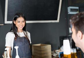 Frau, die Kunden im Café dient foto