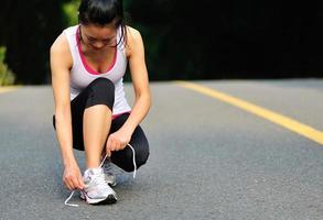 junge Fitnessfrau, die Schnürsenkel auf Straße bindet foto