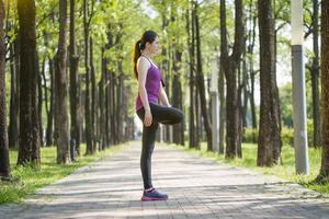 sportliche junge asiatische Frau, die sich nach dem Joggen im Wald ausdehnt foto