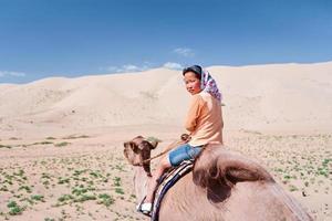 junges Mädchen reitet auf dem Kamel foto