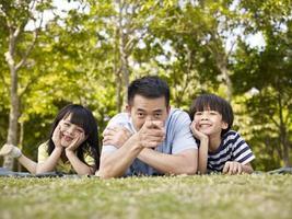 asiatischer Vater und Kinder haben Spaß im Freien
