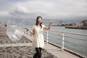 junge glückliche japanische Frau mit Regenschirm foto