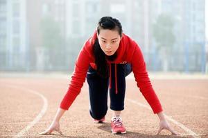 sportliche asiatische Frau in der Startposition auf der Strecke foto