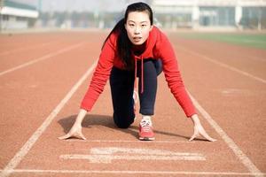 sportliche asiatische Frau in der Startposition auf der Strecke