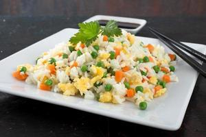 gekochter Reis des chinesischen Essens auf dunklem Hintergrund der Platte foto