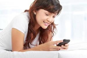Frau SMS am Telefon foto