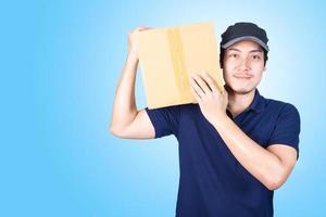 lächelnder hübscher asiatischer Zusteller, der Paket gibt und trägt foto