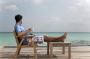 Mann, der Kaffee an Deck am Strand trinkt