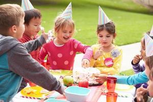 Gruppe von Kindern mit Geburtstagsfeier im Freien