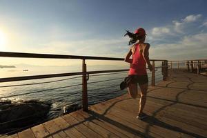 Sportfrau des gesunden Lebensstils, die auf hölzernem Sonnenaufgang der hölzernen Promenade läuft foto