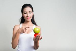 schöne asiatische Frau, die Apfel und Tomate zeigt foto