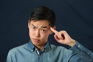 lustiger junger asiatischer Mann, der seinen Zeigefinger zeigt