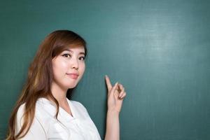 asiatische schöne Frau, die vor Tafel mit Geste steht
