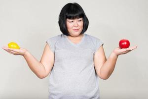 schöne übergewichtige asiatische Frau mit Apfel und Zitrone foto