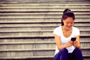 junge Frau mit Smartphone sitzen auf Steintreppen
