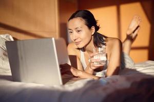 schönes Mädchen, das mit Laptop auf Bett liegt foto