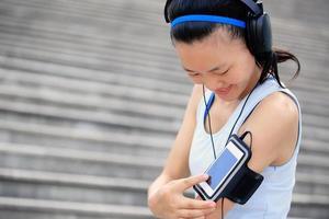 Frau hört Musik in Kopfhörern von Smartphone MP3