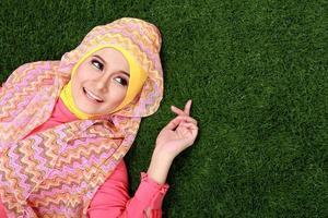 junges muslimisches Mädchen, das auf Gras liegt foto