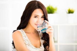 entspannte junge lächelnde Frau, die sauberes Wasser trinkt foto