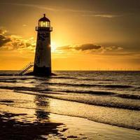 Leuchtturm am Strand bei Sonnenuntergang foto