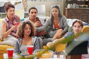 multiethnische Gruppe von Studentenfreunden zu Hause beim Fußball gucken