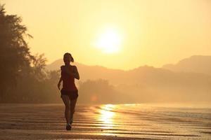 junge Fitnessfrau läuft am Strand foto