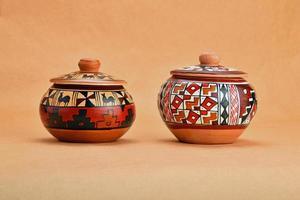 zwei bemalte handgefertigte Keramiktöpfe mit Deckel auf Kraftpapier