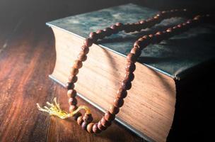 Weinlese gefiltert von Halskette auf Buch, Religionshintergrund.