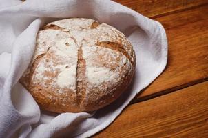 rosiger Laib Brot in weißem Leinenhandtuch gewickelt foto