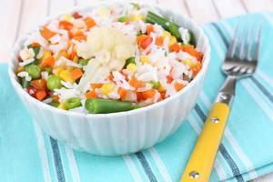 gekochter Reis mit Gemüse auf Holztisch nah oben