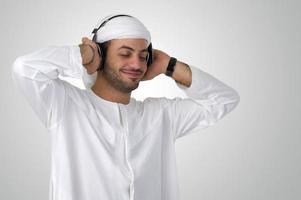 junger glücklicher arabischer Mann mit Kopfhörern, die Musik hören foto