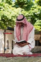 Der muslimische Mann in Dishdasha liest den Koran