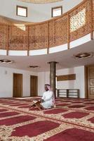 schwarzer Geschäftsmann in Dishdasha liest den Koran