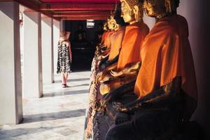 Frau, die Buddha-Statuen im Tempel betrachtet foto