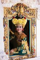 balinesische Tänzerin, die am Fenster sitzt foto