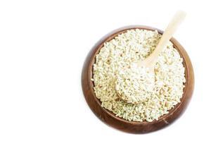 brauner Reis auf Holzlöffel mit hölzernem Hintergrund.
