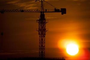 Silhouetten von Baukränen gegen Sonnenaufgang foto