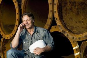 glücklich lächelnder Bauarbeiter auf Handy. foto