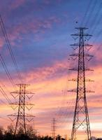 Paralleler Hochspannungs-Strommast am orangefarbenen Himmel.